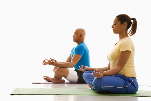 Side view of mid adult multiethnic man and woman sitting in lotus position on exercise mats with eyes closed and legs crossed. : Stock Photo