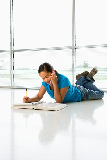 Stock Photo: 4184R-13337 Asian preteen girl lying on floor doing homework while talking on cell phone.