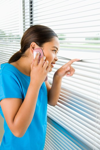 Side view of Asian preteen girl looking through blinds out window while talking on cell phone. : Stock Photo
