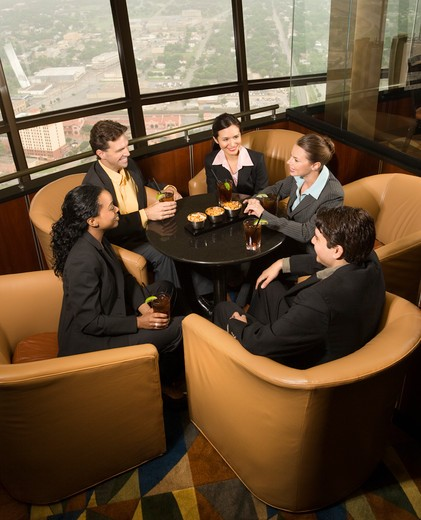 Ethnically diverse businesspeople sitting at table in restaurant talking. : Stock Photo