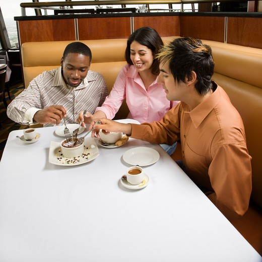 Small group of mid adult friends sharing dessert at a restaurant. : Stock Photo