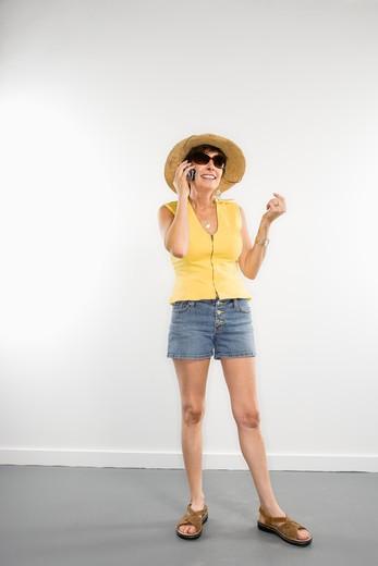 Portrait of pretty Caucasian woman in summer attire talking on cellphone. : Stock Photo