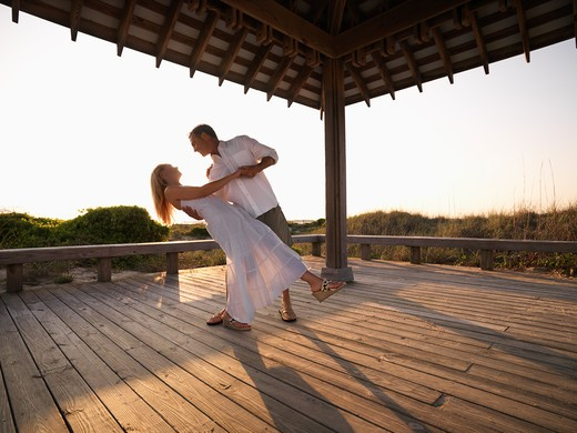 Caucasian couple dancing under gazebo at the beach. : Stock Photo