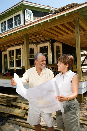 Couple holding building plans on construction site.  Vertically framed shot. : Stock Photo