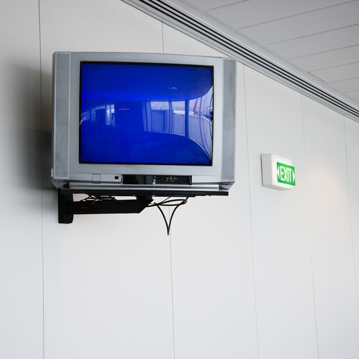 Monitor mounted to wall next to exit sign in airport : Stock Photo