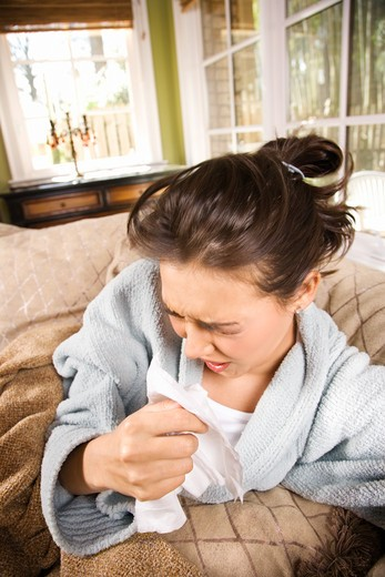 Young ill woman in bathrobe sneezes into a tissue. Vertical shot. : Stock Photo