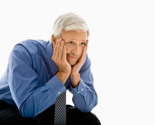 Middle aged Caucasian man with head resting in hands looking bored. : Stock Photo