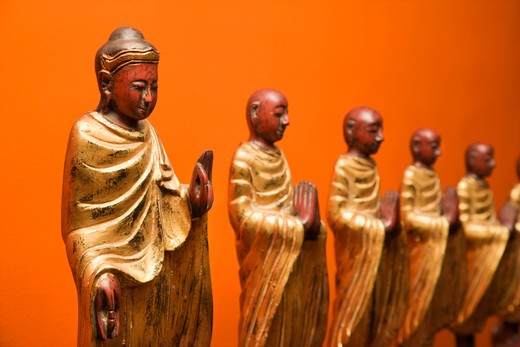 Stock Photo: 4184R-15558 Wooden statues of Buddha with disciples against orange wall.