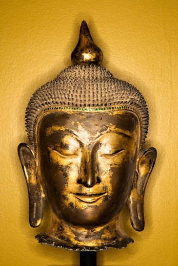 Bronze Buddha head from Thailand against yellow wall. : Stock Photo