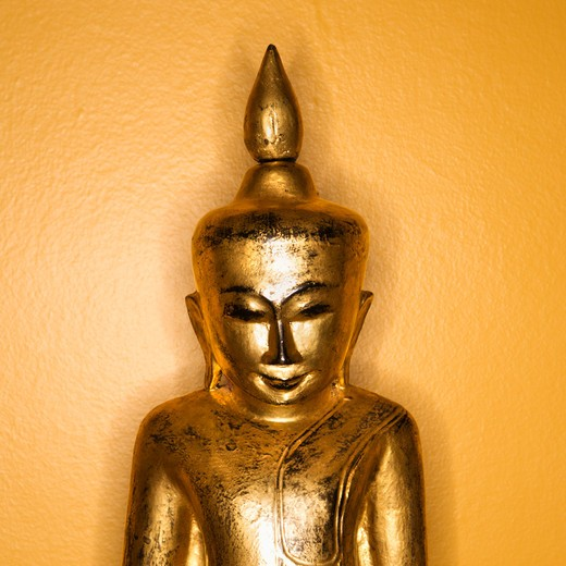 Golden wooden Buddha statue from Burma against yellow wall. : Stock Photo