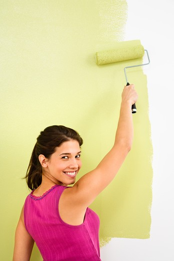 Stock Photo: 4184R-15638 Pretty smiling woman painting interior wall of home with paint roller.