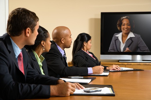 Businesspeople sitting at conference table looking at flat screen display. : Stock Photo