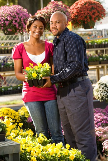 Stock Photo: 4184R-15816 Happy smiling couple picking out flowers at outdoor plant market.