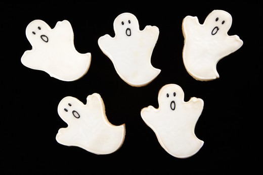 Five sugar cookies in shape of ghosts with decorative icing. : Stock Photo