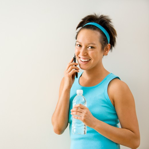 Young woman in fitness clothing holding bottled water talking on cellphone smiling. : Stock Photo