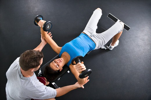 Man assisting woman lifting weights at gym. : Stock Photo