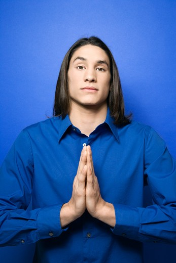 Portrait of Asian-American teen boy with hands pressed together in prayer position standing against blue background. : Stock Photo