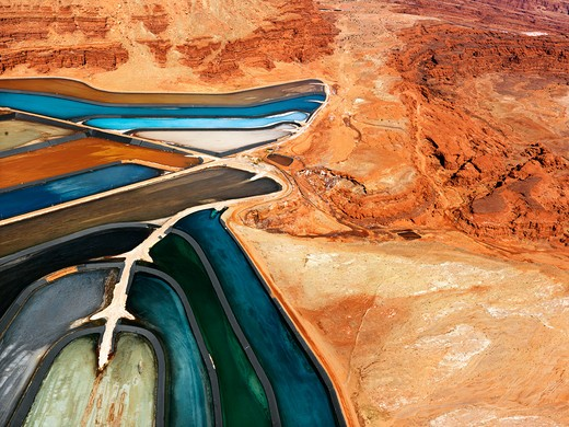 Aerial view of an arid, craggy landscape surrounding tailing ponds. Horizontal shot. : Stock Photo