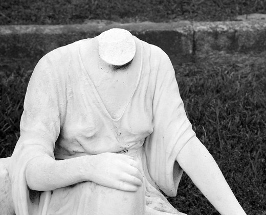 Statue in graveyard of headless woman. : Stock Photo