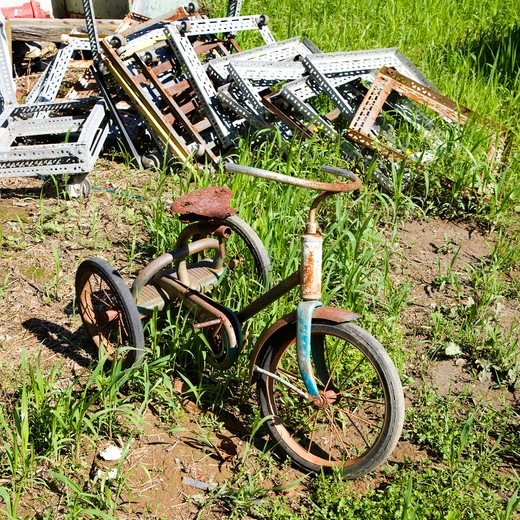 Old abandoned tricycle in grassy field next to junk pile : Stock Photo