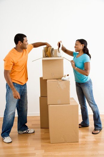 Stock Photo: 4184R-17079 African American male and female couple packing cardboard boxes with shoes.