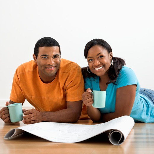 African American male and female couple with architectural  blueprints drinking coffee. : Stock Photo