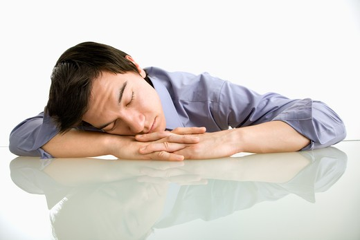 Stock Photo: 4184R-17274 Asian businessman sleeping on desk in the office.