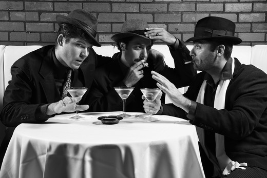 Stock Photo: 4184R-2132 Three Caucasian prime adult males in retro suits sitting at table drinking and smoking and talking.
