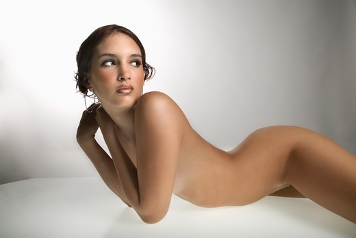 Nude Caucasian young adult woman lying on stomach and looking over shoulder. : Stock Photo