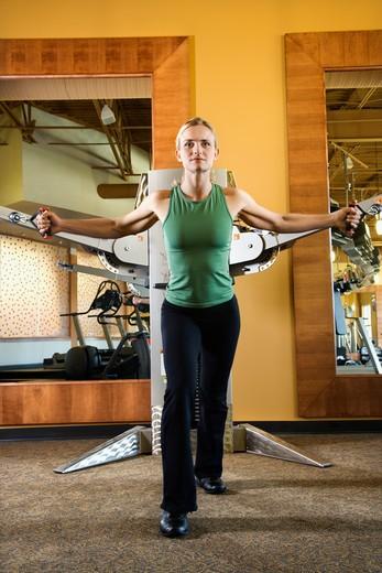 Stock Photo: 4184R-2274 Prime adult Caucasian female using exercise equipment at gym.