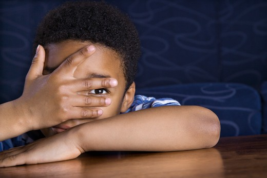 Young African American boy peeks through his fingers as he sits at a coffee table. Horizontal shot. : Stock Photo