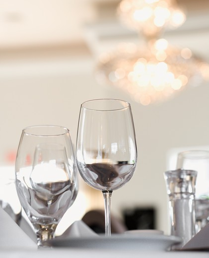 Water and wine glasses on an elegant restaurant dining table. Vertical shot. : Stock Photo