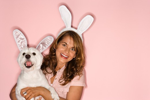 Stock Photo: 4184R-3103 Caucasian prime adult female and white terrier dog wearing rabbit ears.