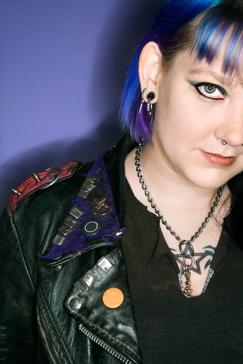 Stock Photo: 4184R-3358 Portrait of Caucasian woman with blue hair and black leather jacket against blue background.