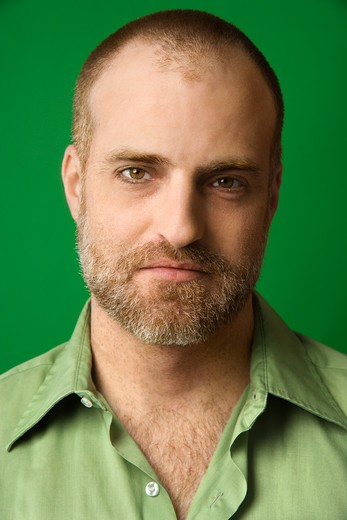 Head and shoulder portrait of Caucasian man with receding hairline and beard against green background. : Stock Photo