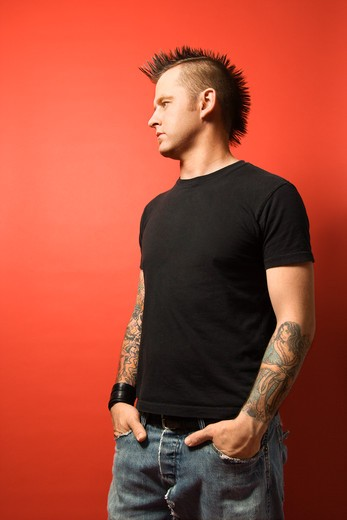 Caucasian man with mohawk and tattoos standing with hands in pockets against orange background. : Stock Photo