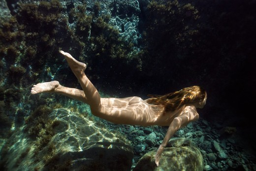 Underwater view of young Asian nude woman swimming away. : Stock Photo