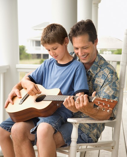Stock Photo: 4184R-4898 Son sits on his father's lap while playing guitar. Vertical shot.