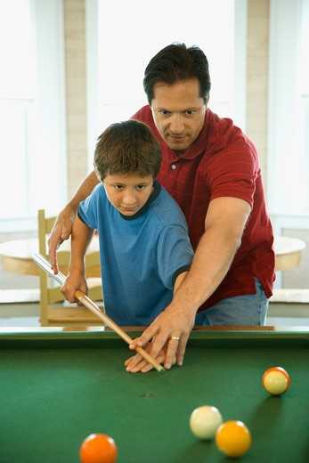 Man shooting game of pool with young boy.  Vertically framed shot. : Stock Photo