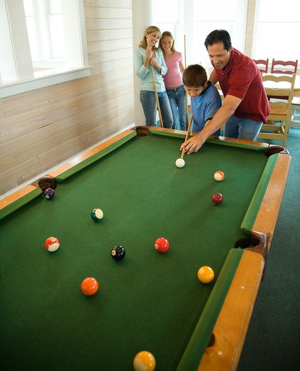 Man and boy shooting pool with woman and girl in background. Vertically framed shot. : Stock Photo