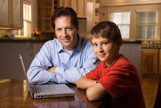 Stock Photo: 4184R-4999 Father and son sitting at dining room table with wireless laptop computer.