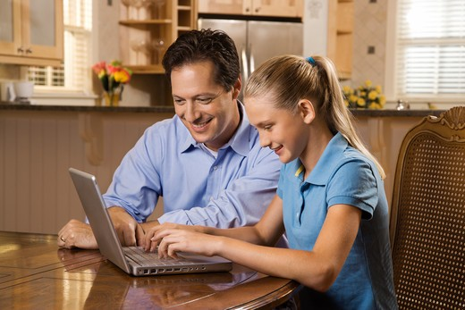 Smiling father and daughter sitting at dining room table working on laptop. : Stock Photo