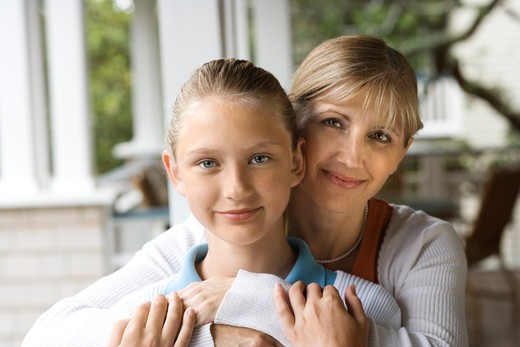 Caucasian mid-adult mother hugging pre-teen daughter. : Stock Photo