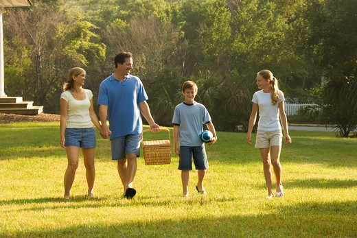 Caucasian family of four walking in park carrying picnic basket. : Stock Photo