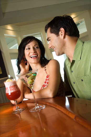 Stock Photo: 4184R-5301 Couple have a good time sitting at a bar with drinks. Vertical shot.