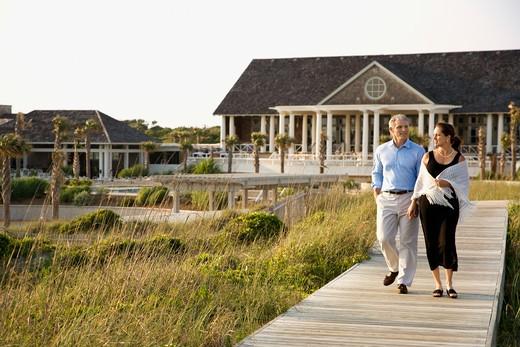 Caucasian mid-adult couple walking on walkway near beach home. : Stock Photo