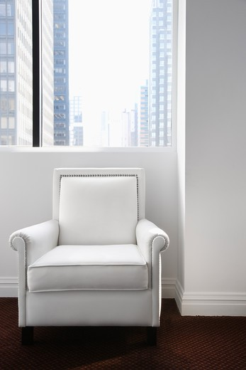 White leather chair sitting underneath a window with a view of buildings in the background. Vertical shot. : Stock Photo