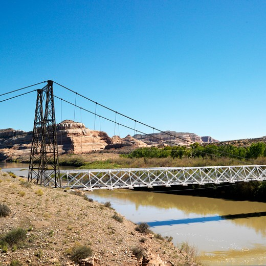Suspension bridge over river with rock cliffs in Utah. : Stock Photo