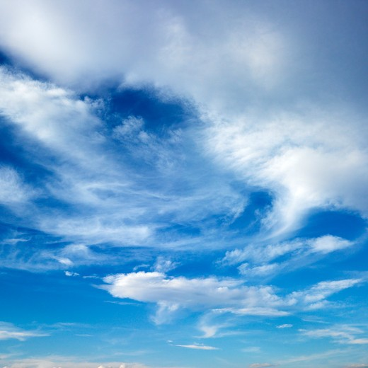 Wispy cloud formations against clear blue sky. : Stock Photo