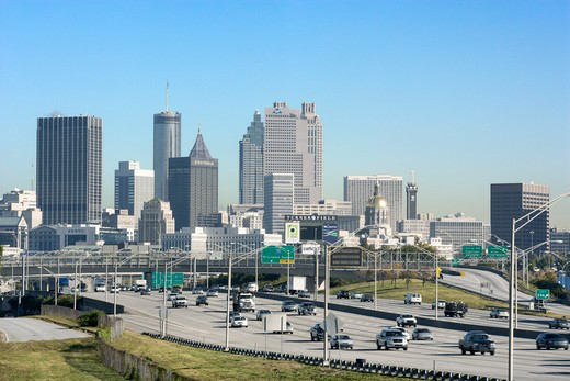 Traffic on a multi-lane freeway heading into and out of downtown Atlanta. Horizontal shot. : Stock Photo